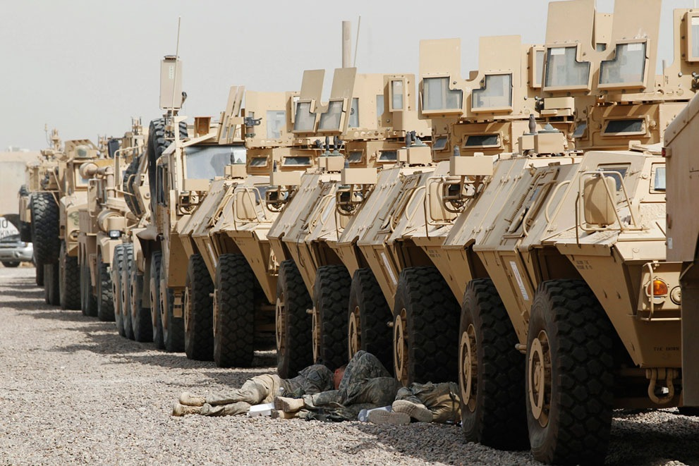 Американские солдаты отдыхают в тени бронетехники в лагере Свободы в Багдаде, 30 сентября 2011 года.