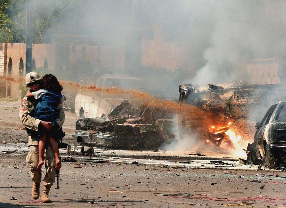 Американский солдат несет иракскую девочку подальше от места трех взрывов 30 сентября 2004 в Багдаде.