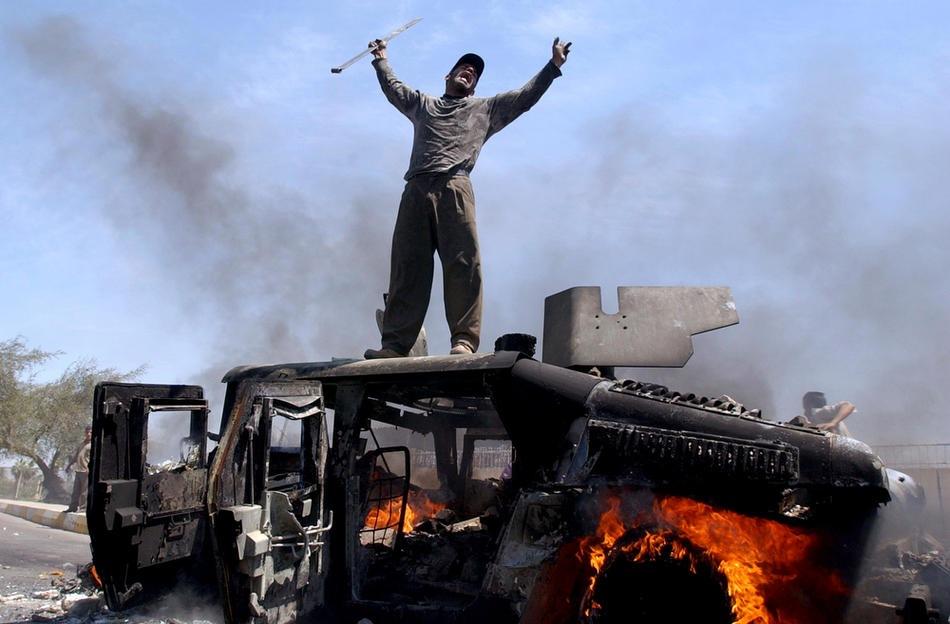 Иракец радуется на крыше горящего автомобиля армии США, в северной части Багдада, 26 апреля 2004 г.