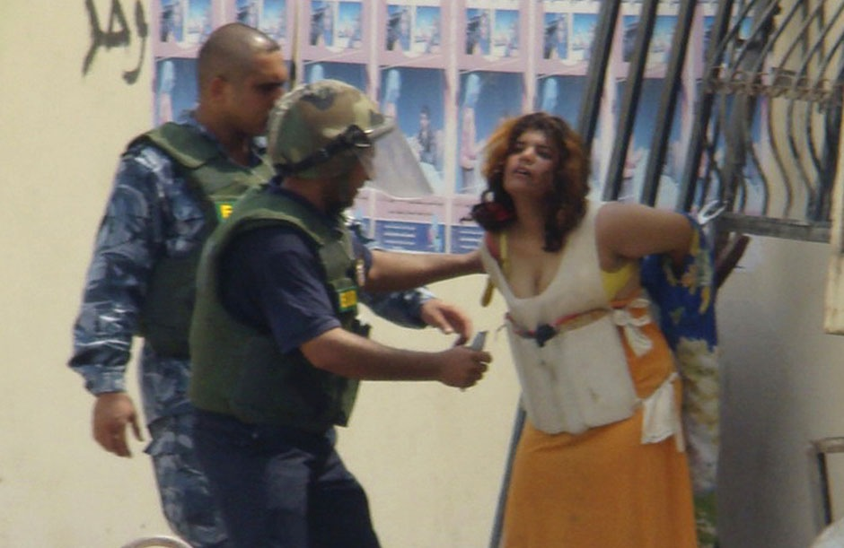 Иракские полицеские снимают с женщины пояс со взрывчаткой, 24 августа 2008 года.