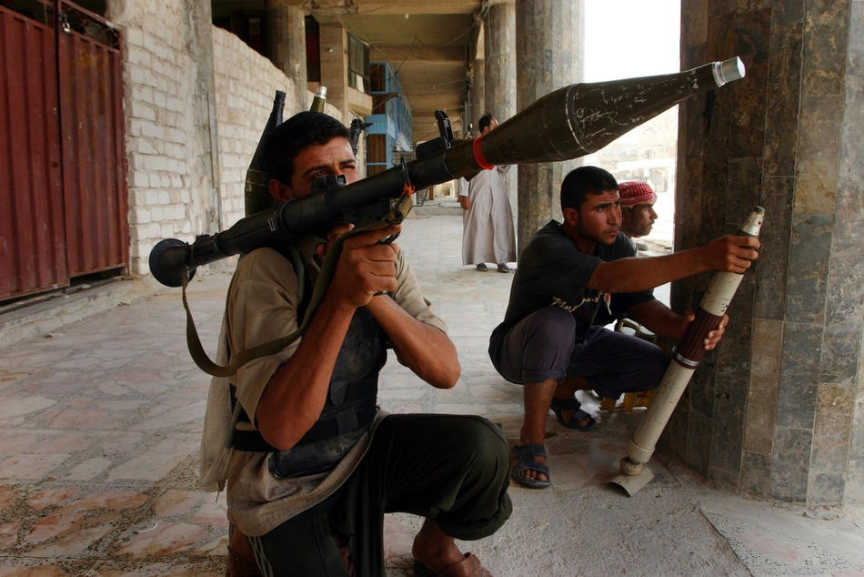 Иракские шиитские милиционеры готовятся к выстрелу во время столкновения с морскими пехотинцами США, 7 августа 2004 в Эн-Наджафе.