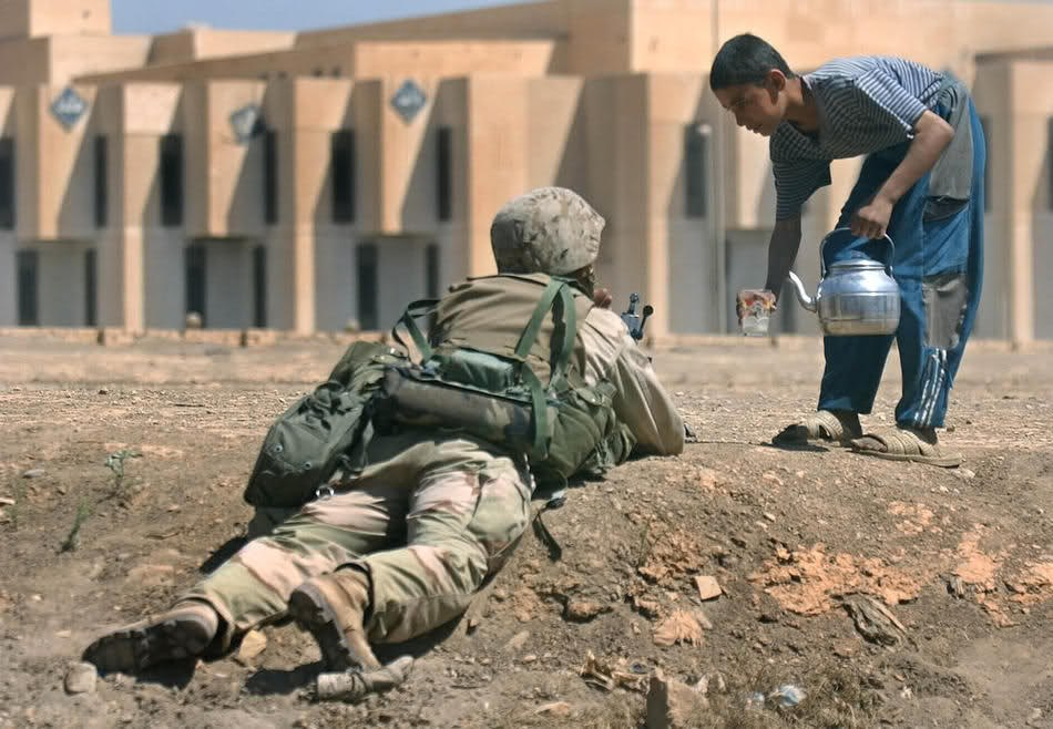 Иракский мальчик предлагает немного воды морскому пехотинцу. Багдад, 11 апреля 2003.
