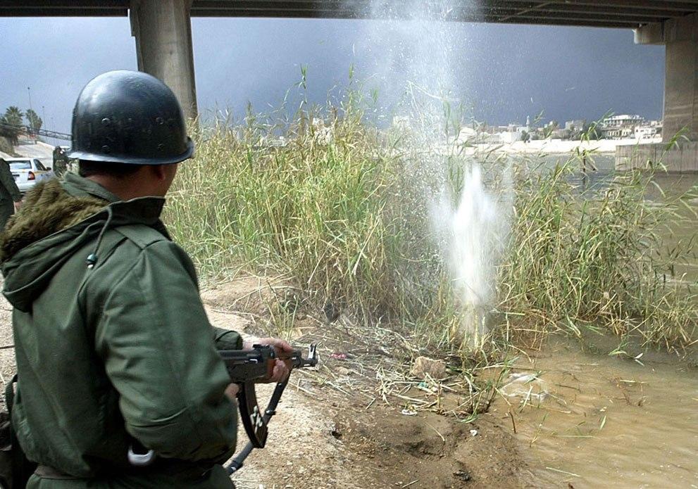Иракский солдат стреляет на берегу реки Тигр в Багдаде, 23 марта 2003