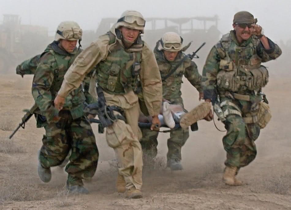 Морпехи эвакуируют раненого на дороге к югу от Багдада, 3 апреля 2003