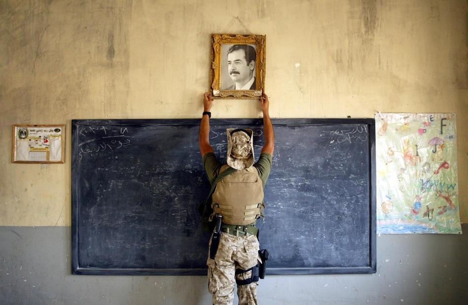 Морпех США снимает фото Саддама Хусейна в школе 16 апреля 2003 года в Эль-Кут.
