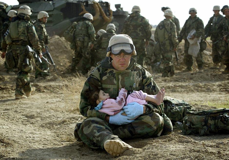 Полевой медик первого класса Ричард Барнетт из 1-й дивизии морской пехоты США держит на руках иракского ребенка, 29 марта 2003 года.