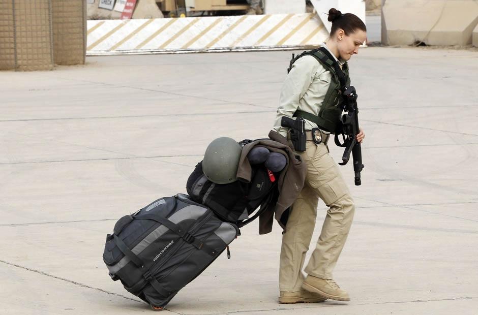 Член американского персонала везет багаж на бывшей американской авиабазе Sather, неподалеку от Багдада 15 декабря 2011.