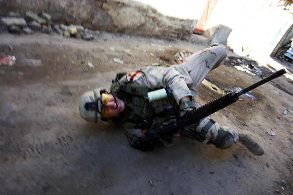 падает на землю, после ранения во время перестрелки 16 февраля 2005 года в Багдаде.