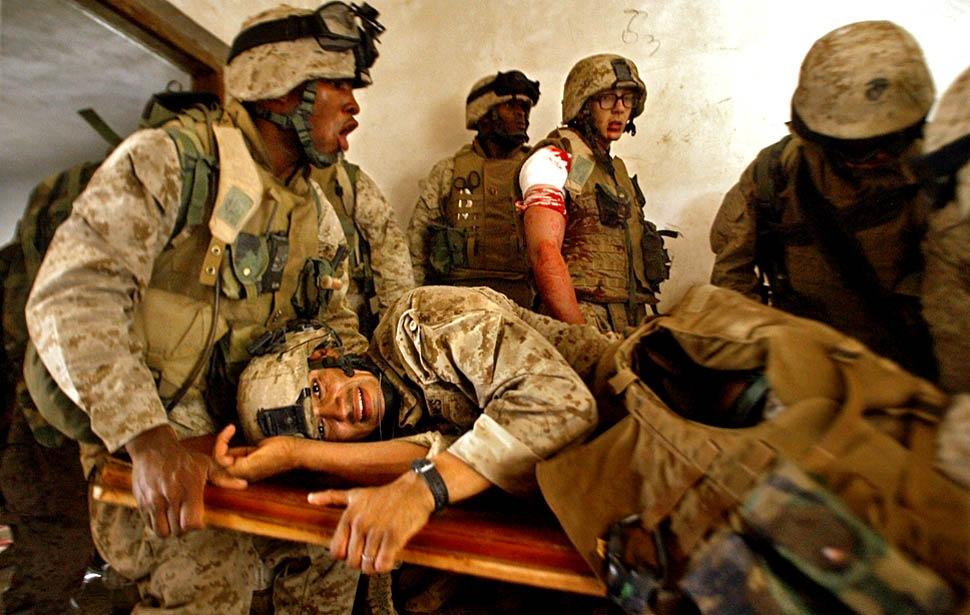 помогает нести раненого сержанта Josue Магана из дома, под огнем повстанцев в апреле 2004 года.