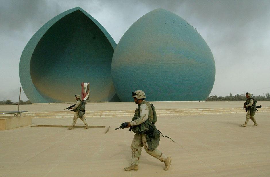 проходят мимо Памятника мученикам во время операции по захвату центральной части Багдада, 9 апреля 2003 года.